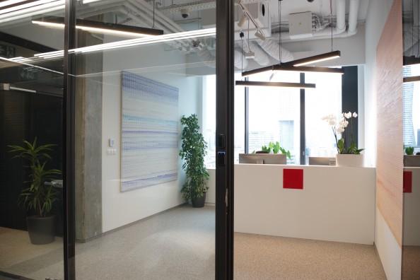 Prace zawieszone na hakach w ścianie, ekspozycja obrazów w biurze