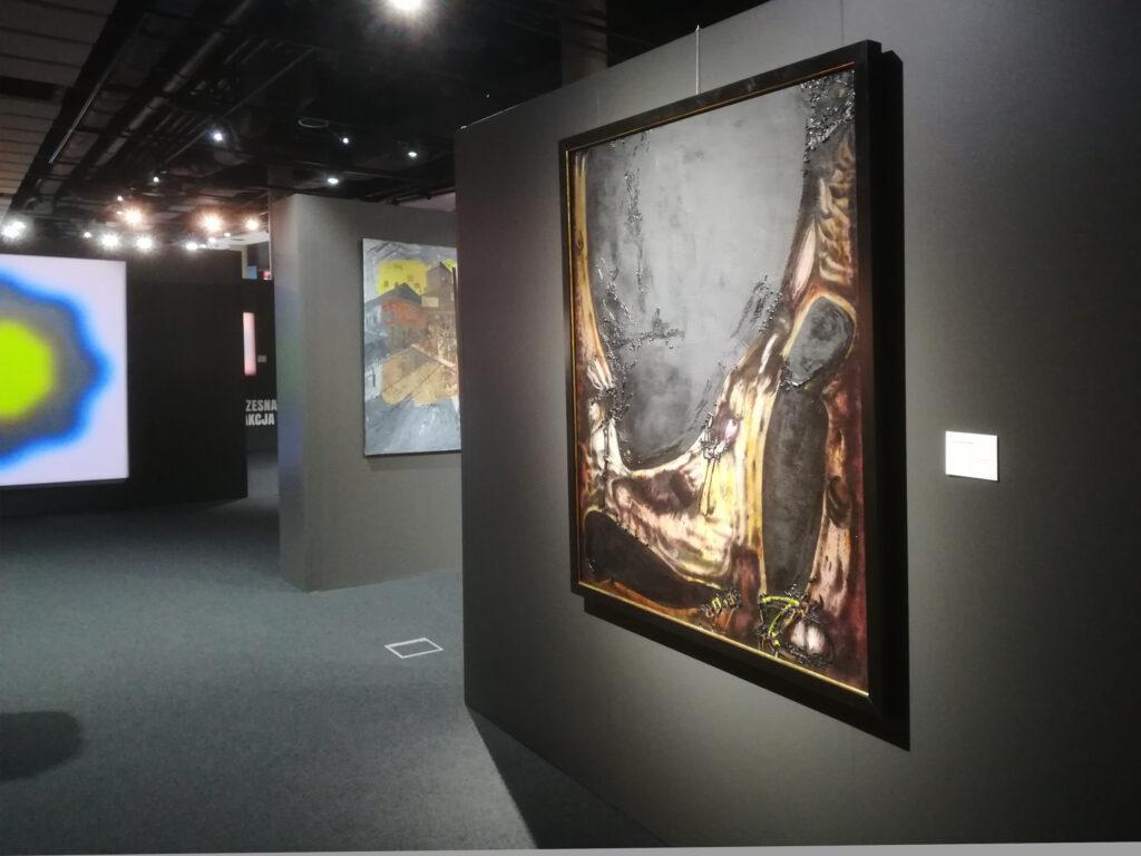 Wystawa przedaukcyjna w Desie, obraz Tadeusza Brzozowskiego, w tle optyczne koło Wojciecha Fangora